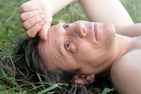 An elderly man with lies sunbathing in the grass. Portrait of a Russian pensioner