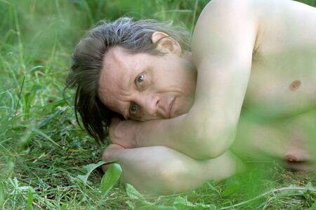 A sad elderly man with a naked torso lies in the grass. Russian Reklamní fotografie