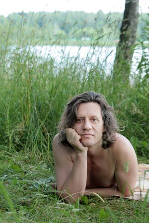 An elderly man with lies sunbathes in the grass on the shore. Russian, long hair, brunette.