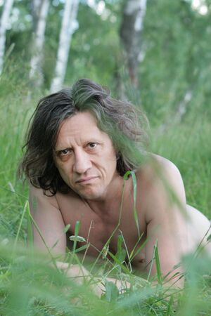 An elderly man with lies sunbathing in the grass. Russian, long hair, brunette. Reklamní fotografie
