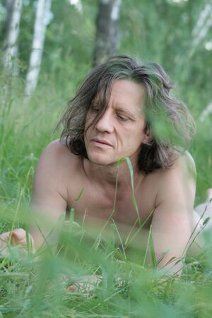 An elderly man with lies sunbathing in the grass. Russian, long hair, brunette