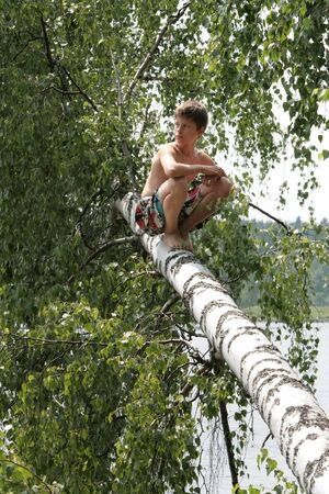 A boy sits on a fallen birch in the leaves. Russian