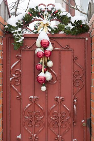 Christmas decorations - balls and spruce branches, over the gate to the house