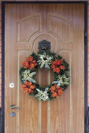 Christmas wreath with artificial Poinsettia on the front door for New Year, Christmas Reklamní fotografie