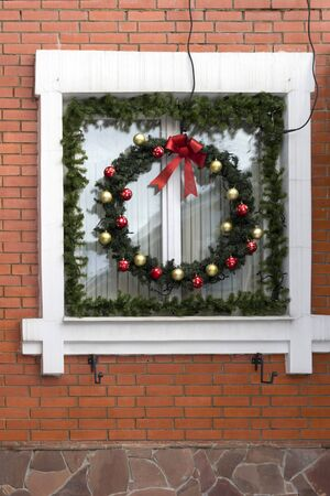 Christmas, New Year wreath hanging on the window. Brick wall Reklamní fotografie