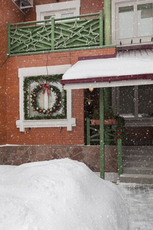 Brick townhouse, cottage with decorations for the New Year. Snowing