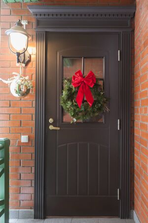 Brown, dark classic door with New Year decorations. The street lamp is on