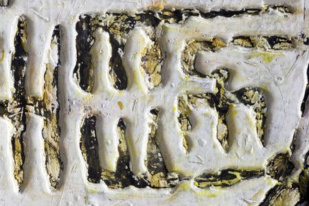 A relief fragment with fantastic ancient text - white and gold. Handwork, ancient art. Reklamní fotografie