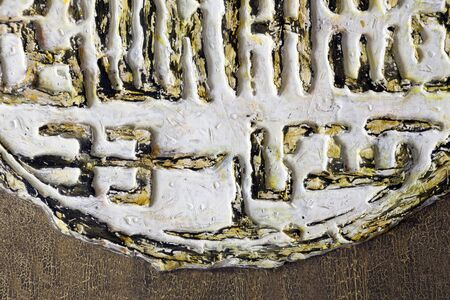 A fragment of the relief in the spirit of Chinese characters - white and gold. Ancient text