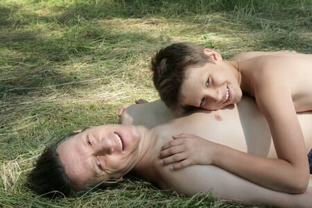 Happy father and son indulge. In summer they lie and sunbathe in the grass. Russians.