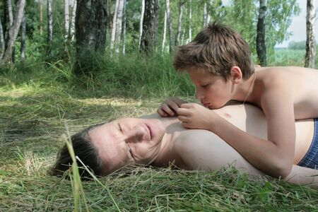 Father and son in the summer lie and sunbathe in the grass in the meadow. Russians. 写真素材