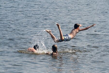 The son jumped into the water from his fathers shoulders. Dad, daughter and son bathe and swim in the lake. Stockfoto