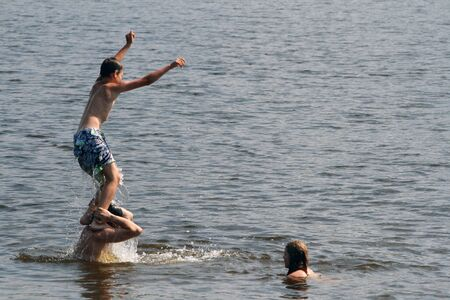 The son jumps into the water from the shoulders of his father. Dad, daughter and son bathe and swim in the lake.