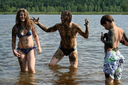 Dad, daughter and son wash away the healing mud in the lake. Russian family on treatment