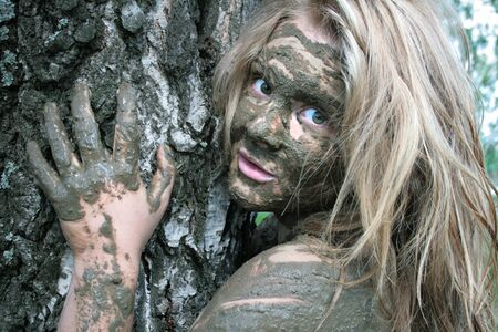 Girl with a mask of mud near a tree trunk in an ecological resort. Beautiful blonde Archivio Fotografico - 138555292