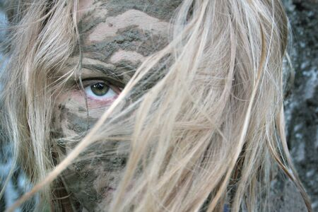 A girl with a mud mask looks through her bangs. Blonde Archivio Fotografico - 138555262