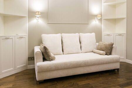 White sofa in a new, bright living room after repair. Laconic interior design Banco de Imagens