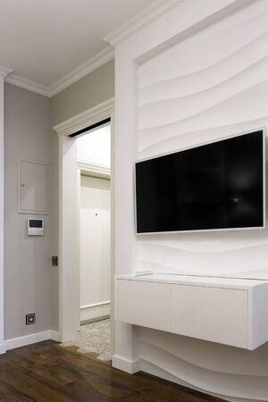 Telewizor na ścianie z panelem 3D. Lakoniczny wystrój wnętrz. Zdjęcie Seryjne