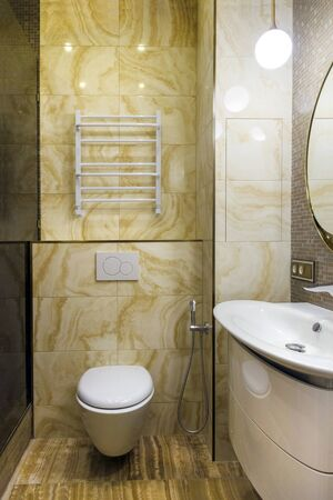 Wall with a toilet with a natural stone finish. Interior design of a bathroom in yellow and white