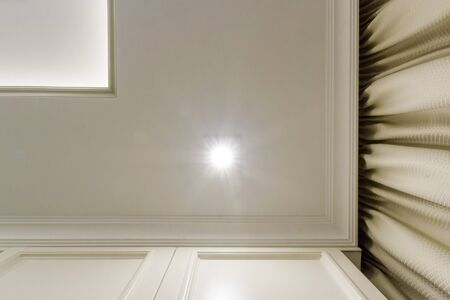 Illuminated ceiling corner bottom view - 2-tier ceiling and beige curtains.