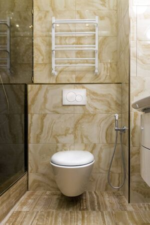 Fragment of a toilet with a natural stone finish. Interior design of a bathroom in yellow and white