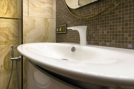 White washbasin with a modern ball valve against a brown mosaic and natural yellow stone tiles Stockfoto