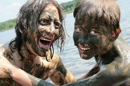 Father and son indulge and have fun in the healing mud. Russians Stockfoto