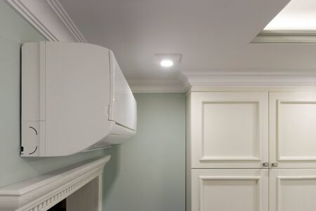 View of the air conditioning above the door and a white wardrobe in the room