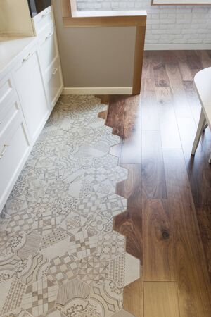 Fashionable mix of tile and parquet in the kitchen. Curved joint of ceramic tiles and wooden floor