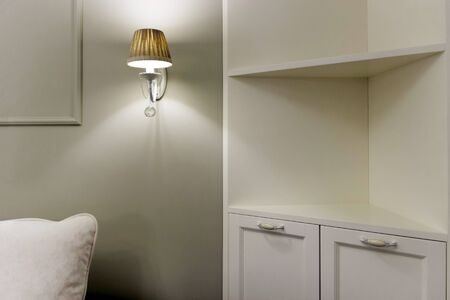 Sconce on the wall near the sofa and cabinet with shelves. Electric lighting
