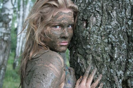 Girl with a mask of mud near a tree trunk in an ecological resort. Beautiful blonde