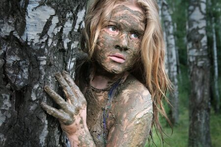 A girl with a mud mask peeps out from behind a birch trunk at an ecological resort. Beautiful blonde