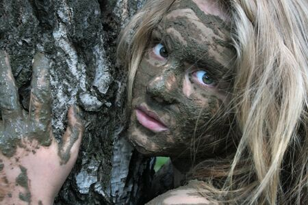 A girl with a mask of mud near the trunk of a birch looks carefully. Beautiful blonde Stockfoto