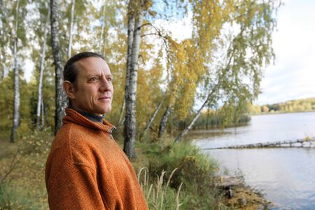 A man in an orange sweater against the background of a river bank with a birch grove. Autumn forest