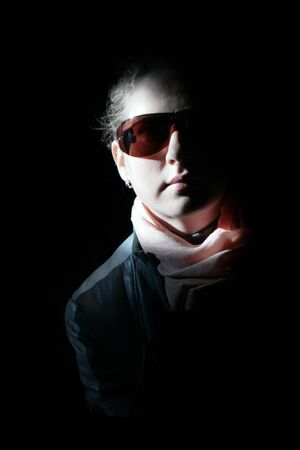 Girl in sunglasses in the rays of sunlight. On a black background.