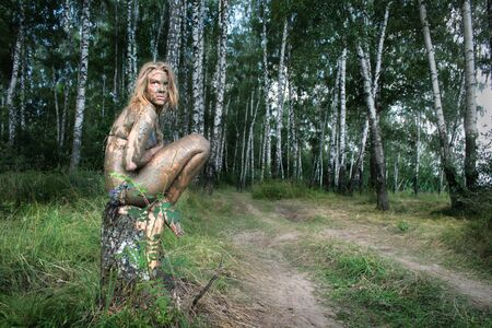 A girl with a mud mask sits on a birch stump at an ecological resort. Beautiful blonde - dirty, wild and alone in the forest