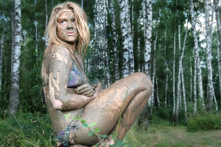 A girl with a mud mask sits in a forest at an ecological resort. Beautiful blonde - dirty, wild and alone in the forest