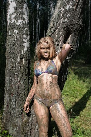 A girl with a mask of mud is standing by the trunk of a birch in an ecological resort. Beautiful blonde Stockfoto