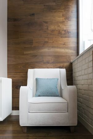 White armchair on the balcony with fashionable parquet wall decoration Stockfoto