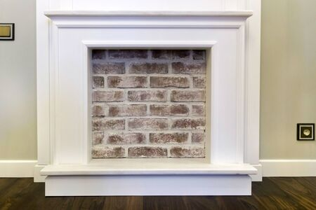 Decorative fireplace on the wall - modern interior. With a red brick.