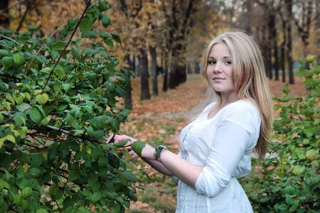 Young blonde girl in autumn in the park near the mock-bush