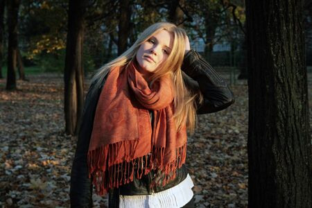 Girl - blonde in an orange scarf in the rays of the autumn sun Stockfoto
