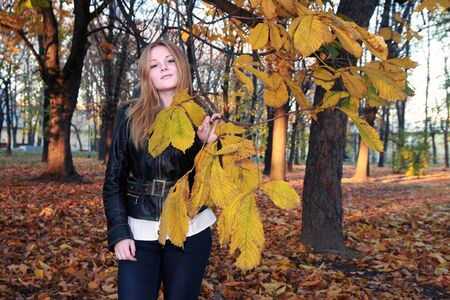 Girl in autumn park with a chestnut branch - yellow leaves