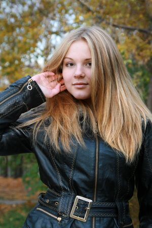 Girl - a natural blonde with long hair in a black jacket straightens her hair