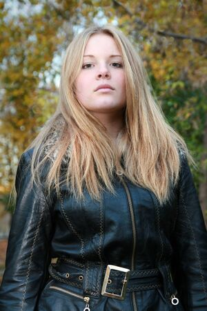 Portrait of a girl - a natural blonde with long hair in a black jacket