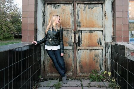 Modern, fashionable girl - blonde stands at the iron gate in the gateway