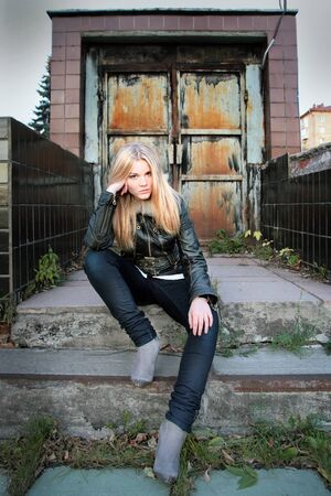 Modern, fashionable girl - blonde sits on the steps in the gateway