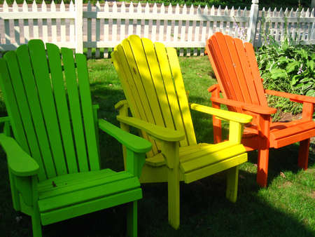 colourful adirondac chairs with picket fence in the back ground Stock Photo