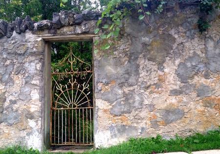 Stone garden wall with ornate iron gate Stock Photo