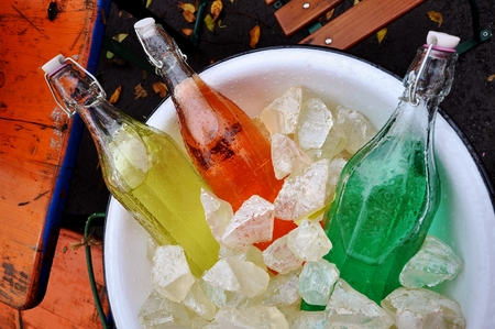 Vintage Soda Bottles filled with colored water in an ice bucket